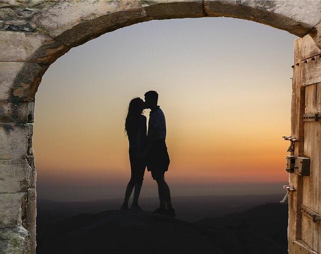 Para całuje sie na tle zachodzącego słońca