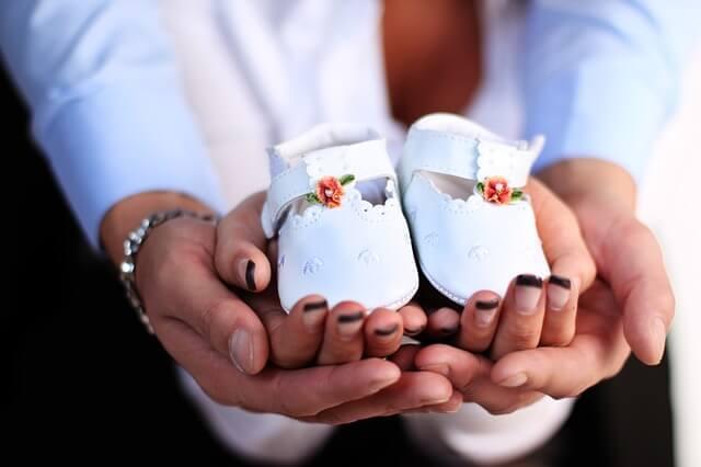 Białe dziecięce buciki na dłoni