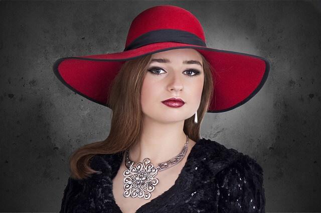 Dziewczyna w czerwonym kapeluszu z kolia na szyi