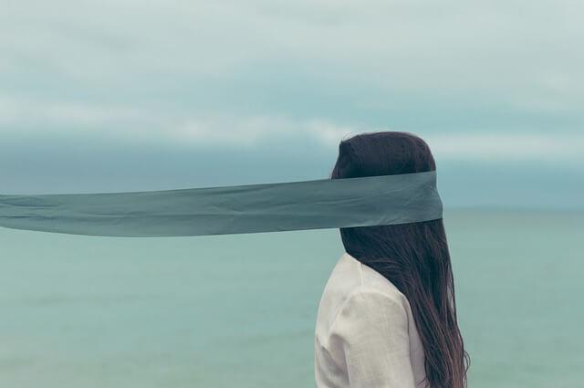 Dziewczyna z niebieska opaską na oczach nad morzem