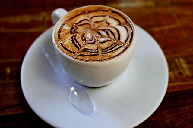 Biała filiżanka z kawą i wzorzystą śmietanką