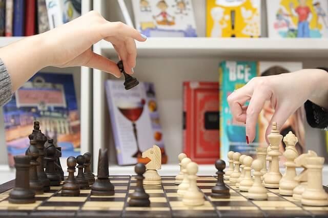 Ręce ustawiają szachy na szachownicy