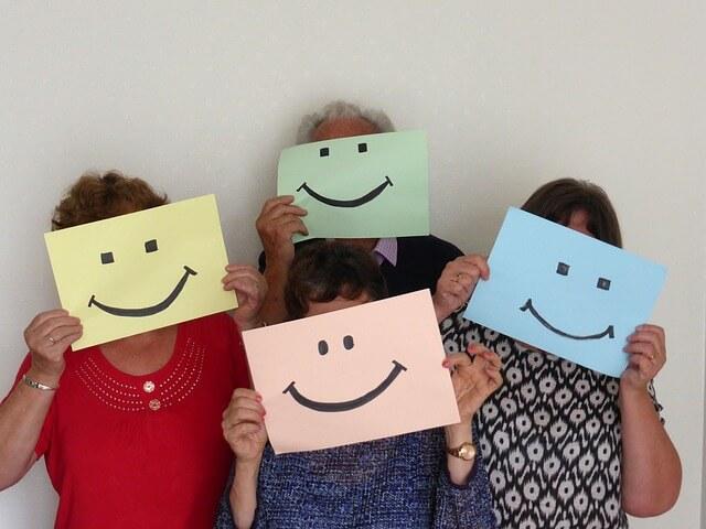 Kobiety trzymają kartoniki z namalowanym uśmiechem