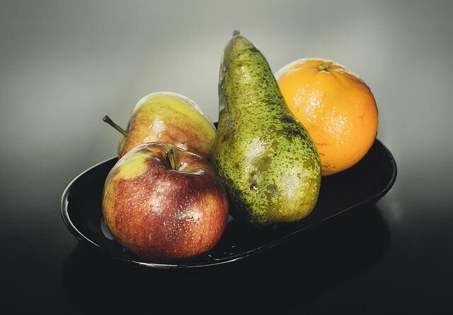 Jabłko, gruszka, pomarańcza na talerzu