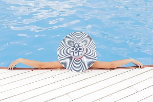 Kobieta w dużym, pasiastym kapeluszu siedzi nad basenem