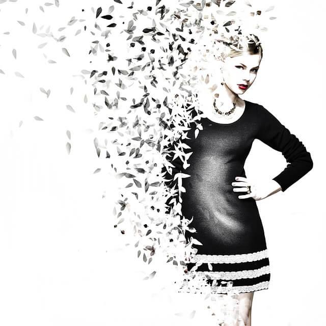 Kobieta w krótkiej, czarnej sukience, z boku liście