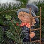Kominiarz zabawka trzyma w ręce drabinę