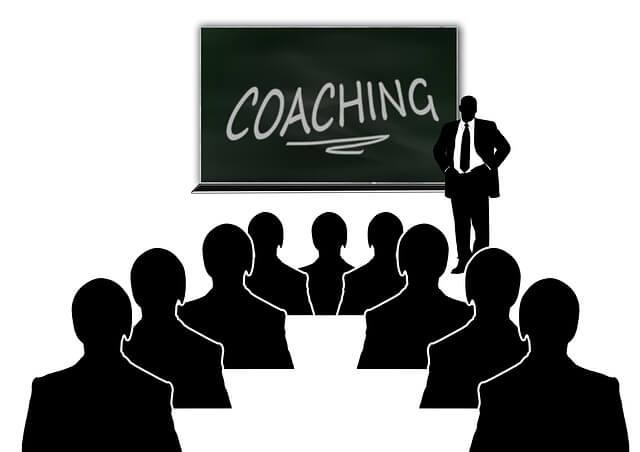 Grupa ludzi siedzi podczas spotkania z trenerem pracy