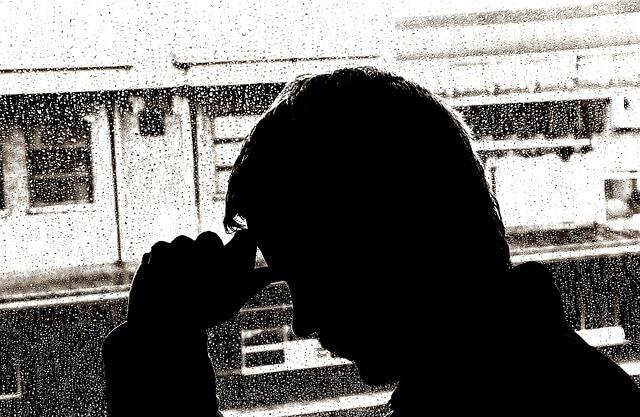 Smutny mężczyzna stojący przy oknie