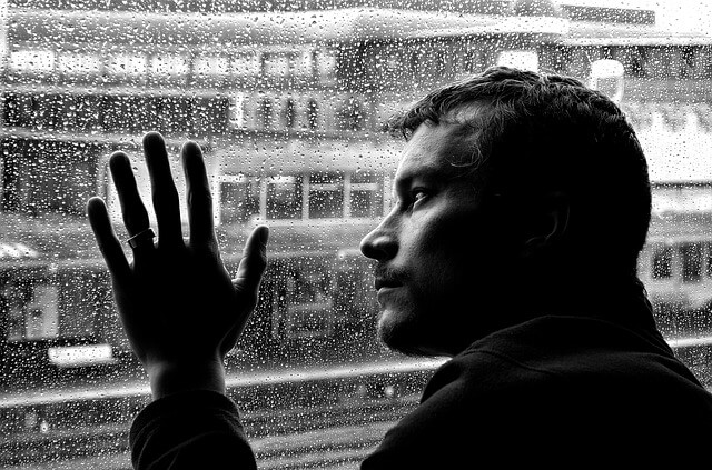 Mężczyzna trzyma dłoń na szybie zalanej deszczem
