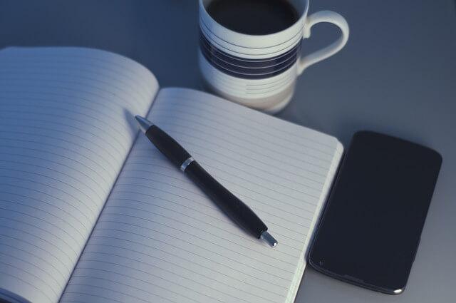 Notatnik, długopis i kawa na biurku