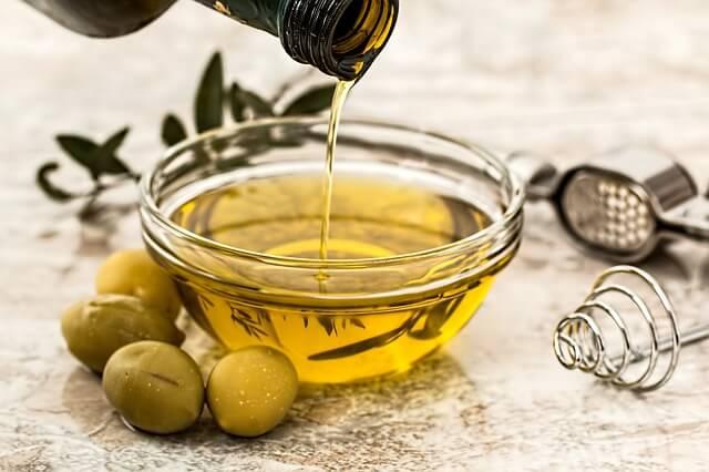 Zielone oliwki obok miski z olejkiem