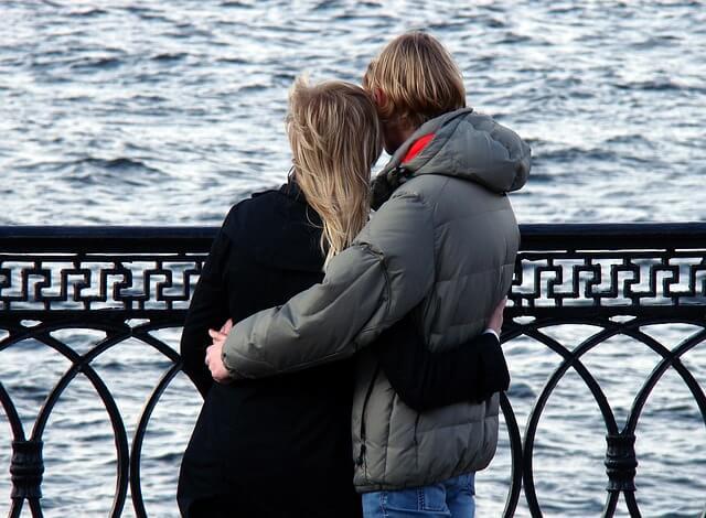kobieta i mężczyzna obejmują się na moście