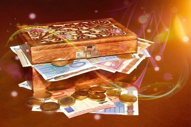 Skrzynia pełna papierowych pieniędzy i monet