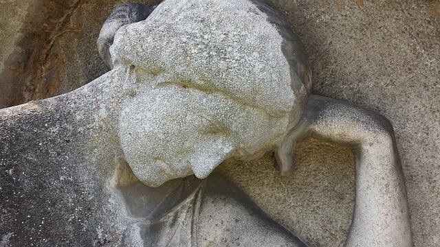 Starożytna rzeźba z pochyloną głową