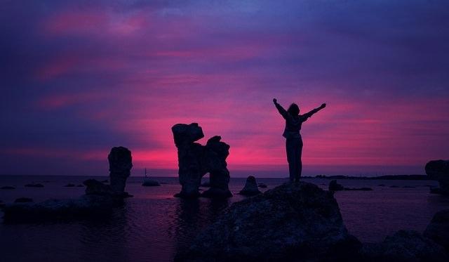 Człowiek stojący na skale z uniesionymi rękami