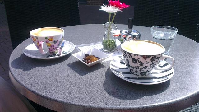 Na kawiarnianym stoliku filiżanki i kwiatki