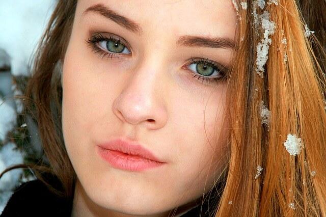 Dziewczyna o zielonych oczach z płatkiem śniegu na włosach